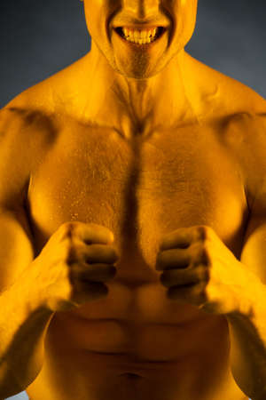 Close up of fit muscular man with golden skin. Standing with strong expression on his face isolated over grey  photo