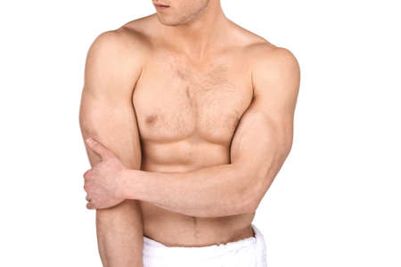 Close up of muscular fit guy body. Standing isolated on white and holding one arm photo