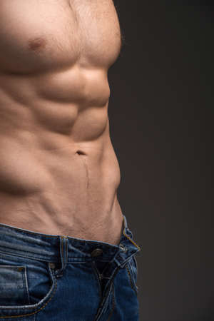 torsos: Close up of Sexy muscular male torso. Wearing unbutton jeans and posing isolated over dark
