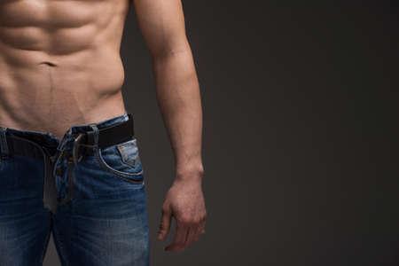 Close up von Sexy muskulöser Mann in Jeans und Oberkörper. Ständigen über grau mit Kopie Platz auf der rechten Seite