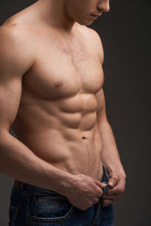 handsome men: Close up of sexy fit man undressing. Standing with torso over dark and unbuttoning jeans Stock Photo