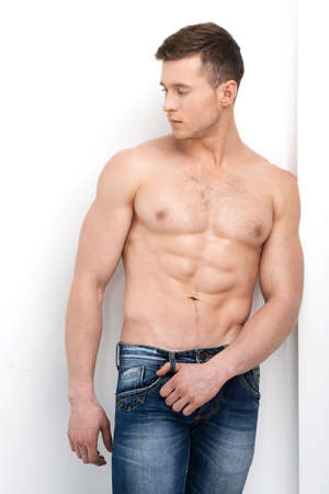 looking away from camera: Sexy shirtless macho posing on camera and looking away. Standing in jeans isolated over white  Stock Photo