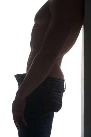 modelos hombres: Primer plano de la silueta del hombre en forma de pantalones vaqueros. Descansando en la pared mientras aislado m�s de blanco Foto de archivo