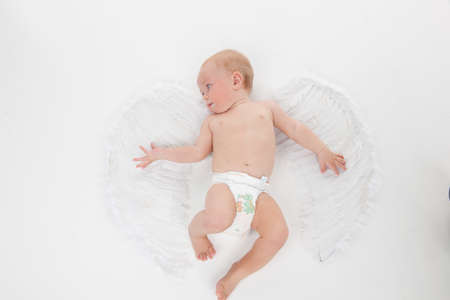 Cute little baby flying with angel wings. Looking away and isolated over white background photo