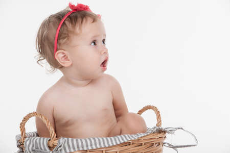 Cut little baby girl in red hoop sitting in basket. Looking away with surprise while isolated over white background photo