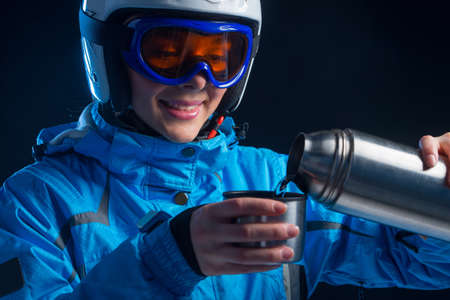 thermos: Close up of smiling beautiful woman pouring hot tea in metal cup out of thermos. Looking away isolated over black background