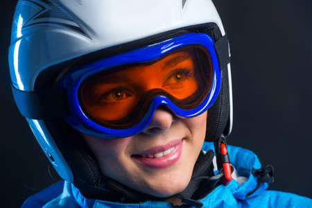 Portrait of happy smiling sportswoman with beautiful eyes in helmets. Standing isolated over black background photo