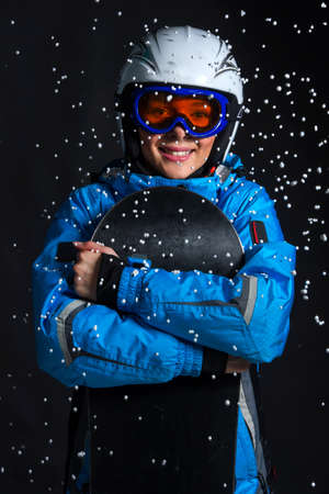 Smiling happy woman standing with snowboard in snow fall. Close up isolated over black background photo