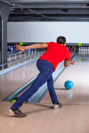 Schreeuwend. Jongeman bowling, hij is het gooien van een bal. Stockfoto
