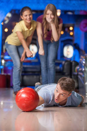 bowling alley: Failure. Man fell while playing bowling with friends