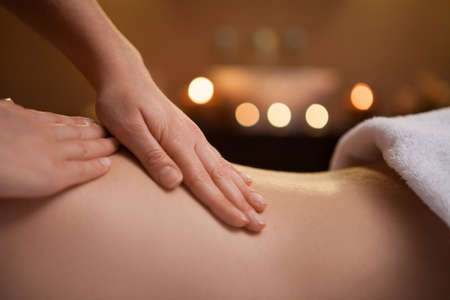 women body: gentle hand massage of girl back. burning candles on background near sink Stock Photo