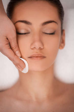 Close-up of gentle make up removal  beautiful young adult woman and cotton pad photo