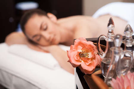 girl is laying on massage table  flower and bottle on table photo