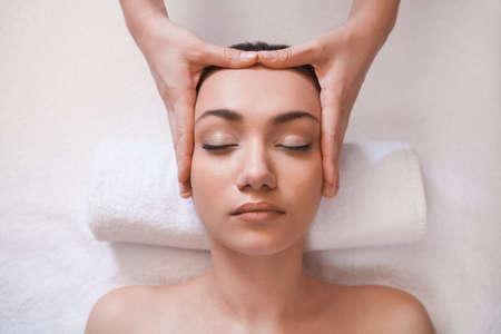 ojos cerrados: hermosa niña recibe masaje en la cabeza la muchacha bonita en la mesa de masaje Foto de archivo