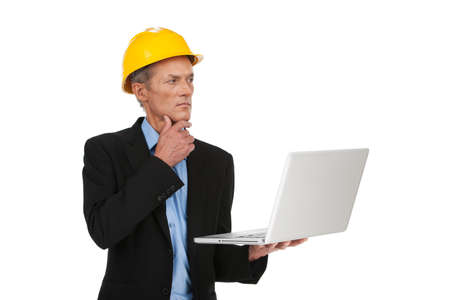 male inspector in helmet working on computer. specialist looking at plan and calculating wall photo