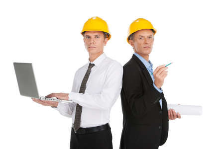 two serious man working at site. men wearing yellow helmet at workplace