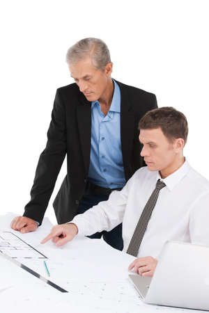 two businessman talking about plan. man pointing at construction site on table photo