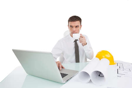 worker drinking tea and using computer. man wearing tie and white shirt photo