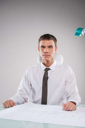 man sitting at desk and reviewing plan. businessman wearing tie working with plan photo