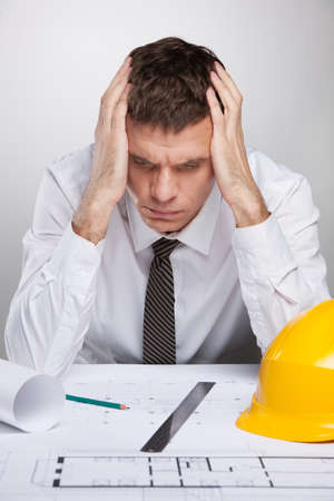 holding the head: professional architect holding head and reading. man sitting at table and studying construction plan