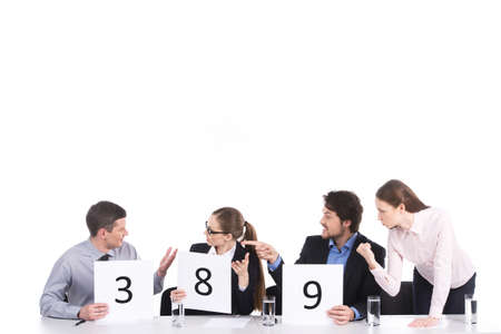 people arguing: heated teamwork and discussion in group of four. three people arguing against one man  Stock Photo