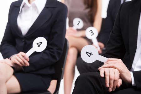 投票黒のスーツを着た人々。男性と女性の番号を保持しているグループ 写真素材