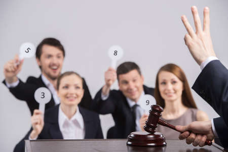 four people raising cards with number. judge counting and holding hammer in hands