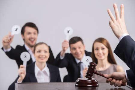 vier Menschen, die Anhebung Karten mit Zahl. Richter Zählen und hält Hammer in der Hand