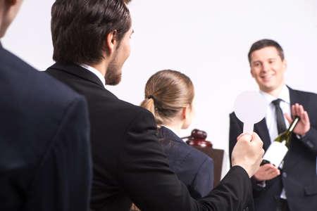 stattlicher Mann mit Flasche Wein. Person verkauft teure Getränke bei einer Auktion