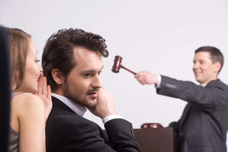 귀에 속삭이는 젊은 아름 다운 갈색 머리. 경매에서 여자에게 듣고 잘 생긴 남자