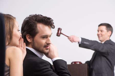 jonge mooie brunette fluisteren in het oor. knappe man luisteren naar vrouw op een veiling