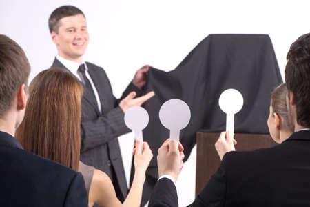 gut aussehender junger Mann die Abdeckung entfernen. Menschen bei einer Auktion Hebe Paddel zusammen Standard-Bild