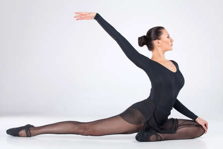 pointes: attractive young ballet dancer dancing. elegant female sitting on floor and stretching