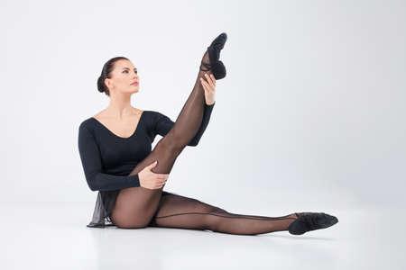 warmers: elegant young dancer stretching leg. beautiful ballet dancer lifting foot