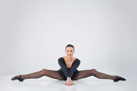 twine: beautiful girl doing side split. attractive athlete stretching on floor and smiling