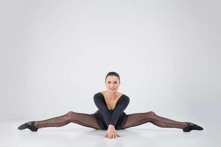 motouz: krásná dívka dělá boční rozkol. atraktivní sportovec strečink na podlaze a usmívající se Reklamní fotografie
