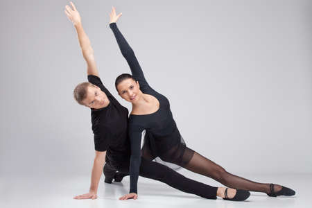 two ballet dancers practicing on white. man and woman dancers leaning on floor photo