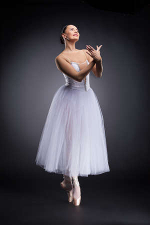 attractive ballet dancer standing and smiling. beautiful ballerina standing tiptoe and practicing photo