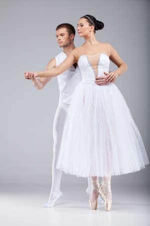 ballet hombres: atractiva pareja de baile de la mano. hermosas bailarinas de ballet de puntillas y mirando Foto de archivo