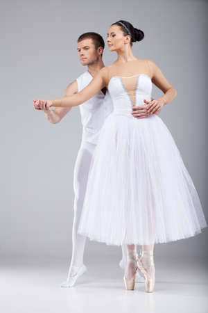 tulle: attractive dancing couple holding hands. beautiful ballet dancers tiptoe and looking