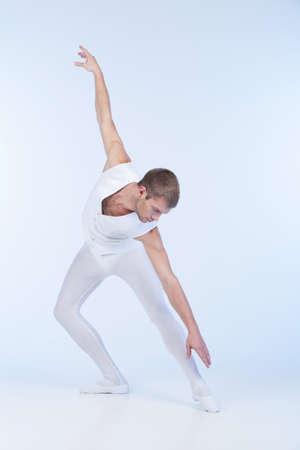 ballet hombres: joven bailarina de ballet practicando en blanco. atractiva bailarina masculino que se realiza en el estudio