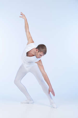 young ballet dancer practicing in white. attractive male ballerina performing in studio photo