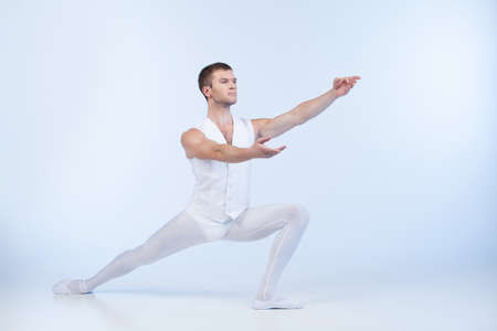 attractive male dancer posing and acting. young ballet dancer practicing in studio photo
