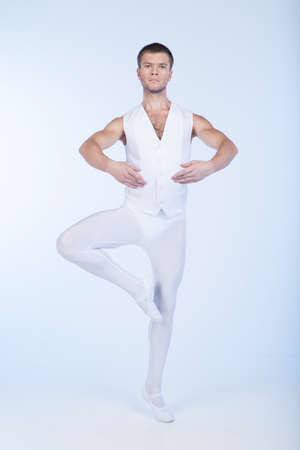 ballet dancer standing with round hands. handsome performer practicing and ready to movement photo