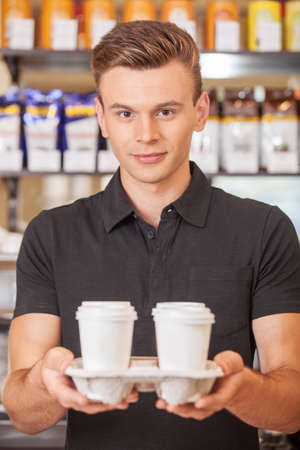 capuccino: young handsome barista holding coffee. handsome worker making coffee with milk Stock Photo