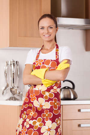 Beautiful young housewife cleaning the kitchen. attractive  housewife standing in apron at kitchen and smiling photo