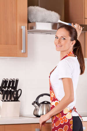 Beautiful young brunette cleaning the kitchen. attractive girl standing in apron and using duster Stock Photo