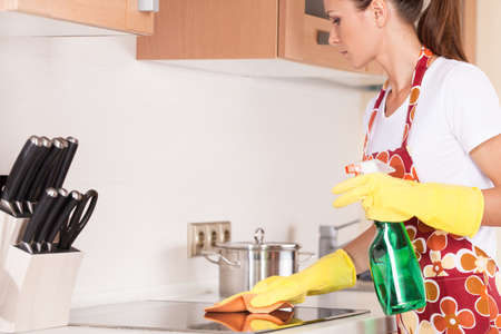Beautiful young brunette cleaning the kitchen. attractive girl standing in apron and using detergents photo