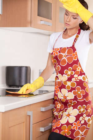 apartment cleaning: Beautiful young brunette cleaning the kitchen. tired girl standing in apron and washing stove