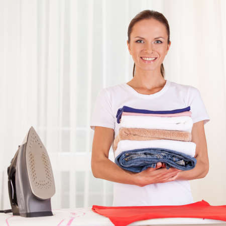 domesticity: Portrait of smiling housewife ironing clothes. waist up housewife standing in bedroom and holding clothes